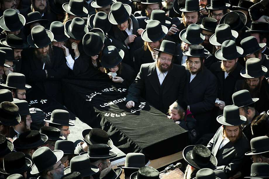Members of the Satmar Orthodox Jewish community congregate for the funeral of two expectant parents who were killed in a car accident, Sunday, March 3, 2013, in the Brooklyn borough of New York. A driver struck the car the couple were riding in early Sunday morning, killing both parents while their baby, who was born prematurely, survived and is in critical condition.  Photo: John Minchillo, Associated Press