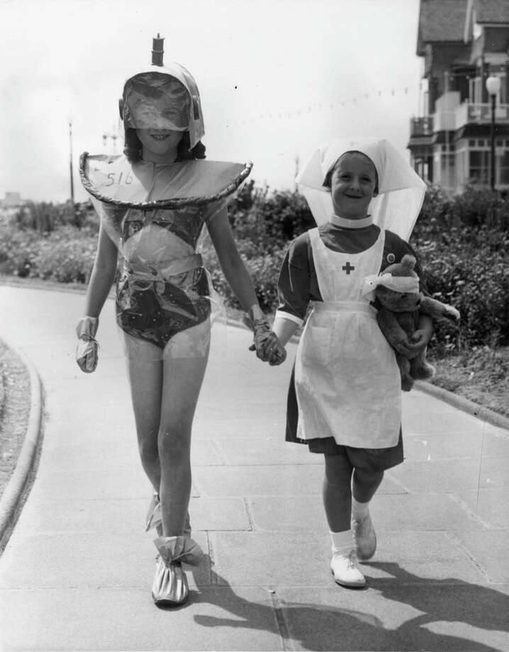 17th August 1955:  Nine year old Ruth Pridmore and five year old Jennifer Gabe on their way to take part in Uncle Bertie's fancy dress competition in Eastbourne, dressed as a martian and a nurse respectively.  (Photo by George W. Hales/Fox Photos/Getty Images) Photo: George W. Hales, Multiple / Hulton Archive