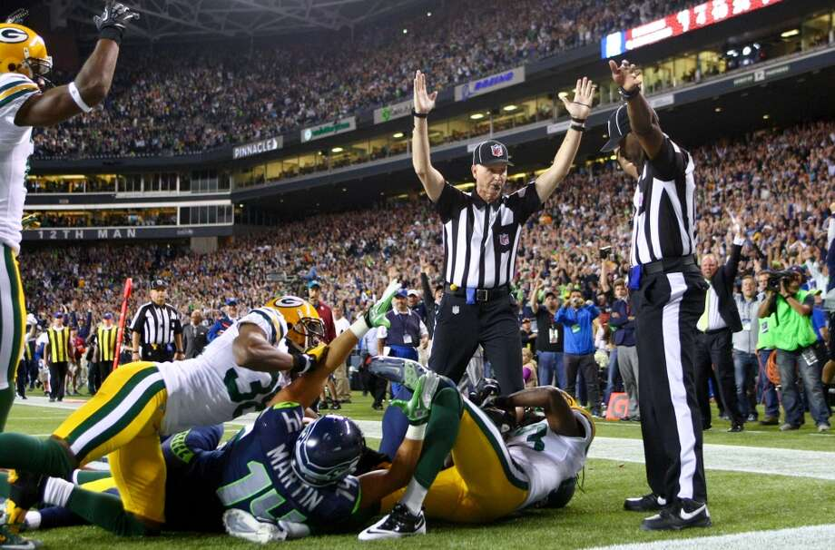 NFL replacement official Lance Easley, center, looks at back judge Derrick Rhone-Dunn as Easley calls a Seahawks touchdown catch by Golden Tate in the final second of the Seahawks-Packers 'Monday Night Football' game on Sept. 24, 2012, at CenturyLink FIeld in Seattle. The controversial call put the Seahawks over the Packers to win 14- 12.