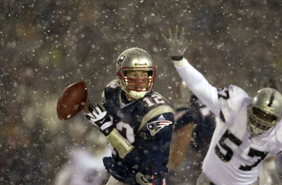 Jan. 19, 2002 -- The 'tuck rule' gamePlaying through heavy snowfall in Boston, the New England Patriots and Oakland Raiders were battling in the AFC divisional playoff game when football fans were treated to one of the most controversial calls in NFL history. With less than two minutes left in the game, Raiders cornerback Charles Woodson sacked Patriots QB Tom Brady (pictured at left) and forced a fumble. Oakland linebacker Greg Biekert recovered the ball, surely sealing a 13-10 victory for the visitors. But upon video review, the officials ruled that Brady was in the process of tucking the ball when he was hit, after pumping a fake pass, which by rule meant it was an incomplete pass and not a fumble. In the aftermath, the obscure ''tuck rule'' quickly became a household phrase. The Patriots ended up keeping the ball and tying the game, sending it to overtime, where the Patriots eventually won 16-13. New England went on to win the Super Bowl that year. Photo: Ezra Shaw, Getty Images / Getty Images North America
