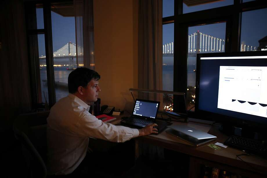 "From a hotel room overlooking the Embarcadero, artist Leo Villareal tests his ""Bay Lights"" art installation on the Bay Bridge. Photo: Carlos Avila Gonzalez, The Chronicle"