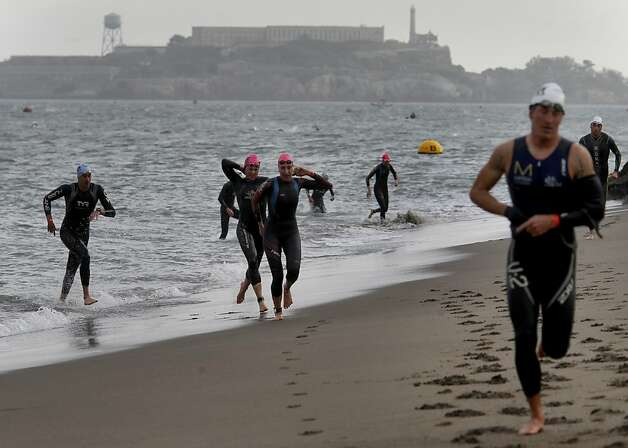 Triathletes emerged from the chilly waters of the bay after jumping off a boat near Alcatraz. The annual Escape from Alcatraz triathlon was held early Sunday morning March 3, 2013 beginning with a swim in the bay and ending with an eight mile run to the finish line at the Marina Green. Photo: Brant Ward, The Chronicle