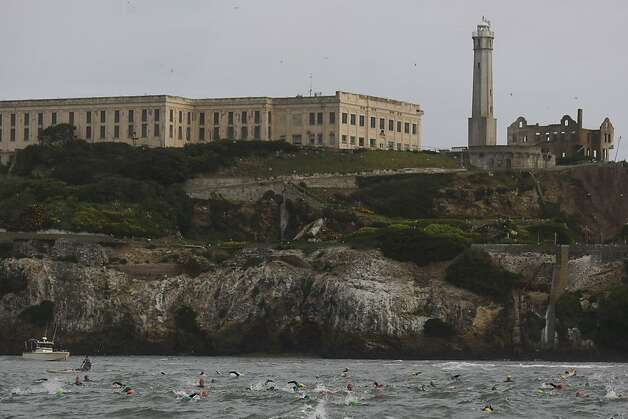 Triathletes swim by Alcatraz during the Escape From Alcatraz Triathlon on Sunday, March 3. The triathlon featured swimming from Alcatraz to the Marina followed by an 18 mile bike ride and an 8 mile run. Photo: James Tensuan, The Chronicle