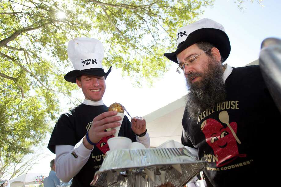 Daniel Gilbert, left, and Rabbi Lazer Lazaroff serve up cones of chili at the Aishel House booth during the 3rd Annual Houston Kosher Chili Cookoff Sunday, March 3, 2013, in Houston. Proceeds from the event benefit a number of non-profit organizations in the Houston Jewish community. Photo: Brett Coomer, Houston Chronicle / © 2013 Houston Chronicle