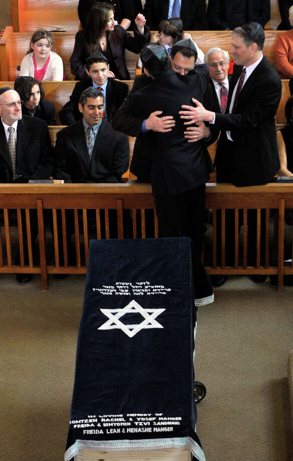 Gov. Dannel P. Malloy hugs Glenn Camhi as Glenn's brother, Keith, puts a hand on the governor's back during the funeral services for Ellen Camhi at Congregation Agudath Shalom in Stamford on Sunday, March 3, 2013. Photo: Jason Rearick / The Advocate