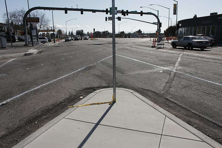 Leftover caution tape marks a pole at Foothill Boulevard and D Street in Hayward, where a car crashed and its passenger died after a nearby incident involving a police officer. Photo: James Tensuan, The Chronicle