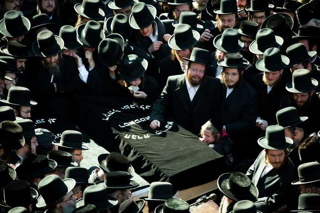 Members of the Satmar Orthodox Jewish community congregate for the funeral of two expectant parents who were killed in a car accident, Sunday, March 3, 2013, in the Brooklyn borough of New York. A driver struck the car the couple were riding in early Sunday morning, killing both parents while their baby, who was born prematurely, survived and is in critical condition. (AP Photo/John Minchillo) Photo: John Minchillo