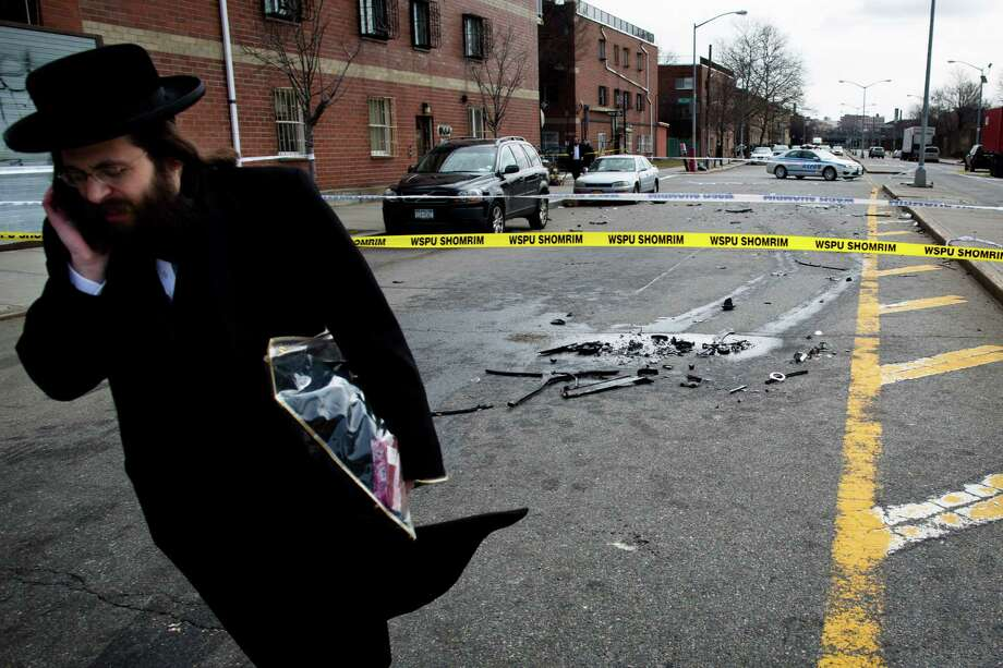 A man walks past debris from a fatal accident that claimed the lives of two expectant parents on their way to the hospital early, Sunday, March 3, 2013, in the Brooklyn borough of New York. A driver struck the car the couple were riding in early Sunday morning, killing both parents while their baby, who was born prematurely, survived and is in critical condition. (AP Photo/John Minchillo) Photo: John Minchillo