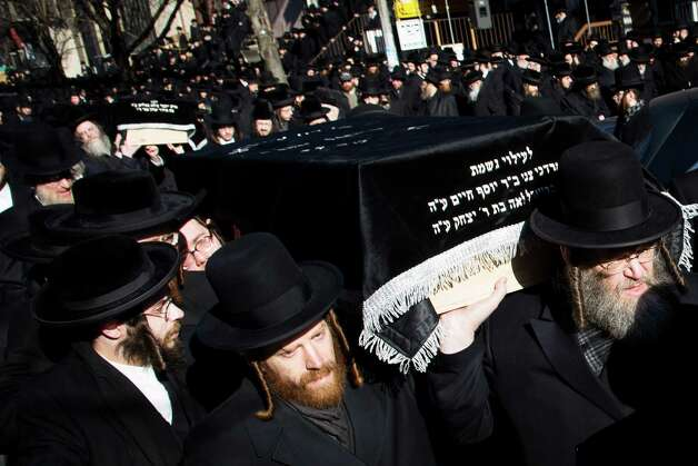 Members of the Satmar Orthodox Jewish community carry the coffins of two expectant parents who were killed in a car accident, Sunday, March 3, 2013, in the Brooklyn borough of New York. A  driver struck the car early Sunday morning, killing both parents while their baby, who was born prematurely, survived and is in critical condition. (AP Photo/John Minchillo) Photo: John Minchillo
