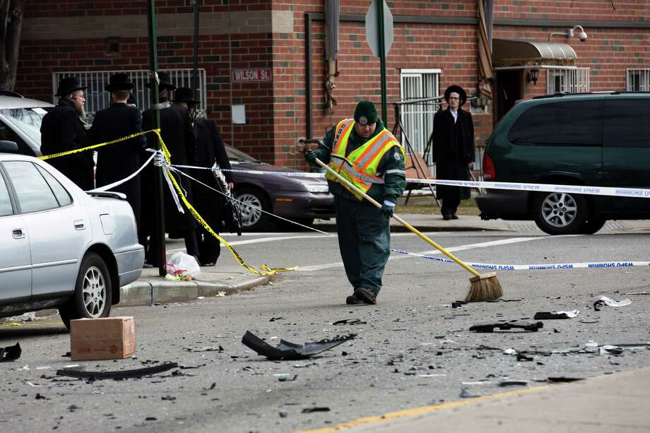 A worker clears debris  from a fatal accident that claimed the lives of two expectant parents, Sunday, March 3, 2013, in the Brooklyn borough of New York. A driver struck the car the couple were riding in early Sunday morning, killing both parents while their baby, who was born prematurely, survived and is in critical condition. (AP Photo/John Minchillo) Photo: John Minchillo