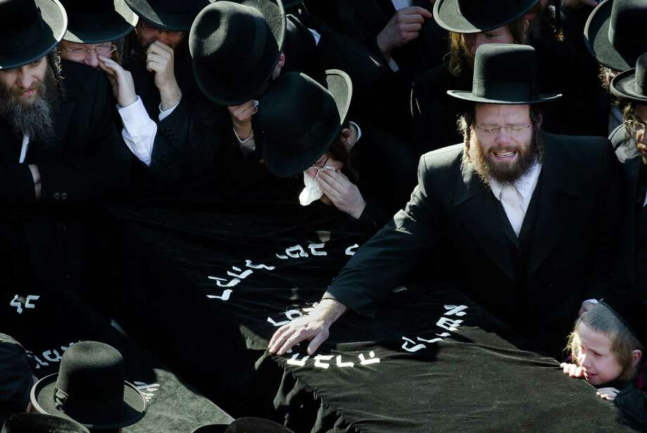 Members of the Satmar Orthodox Jewish community grieve over the coffins at the funeral for two expectant parents who were killed in a car accident, Sunday, March 3, 2013, in the Brooklyn borough of New York. A driver struck the car early Sunday morning, killing both parents while their baby, who was born prematurely, survived and is in critical condition. (AP Photo/John Minchillo) Photo: John Minchillo