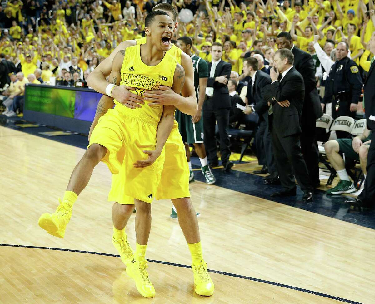 Michigan's Trey Burke gets a hero's hug from teammate Mitch McGary after Burke recorded two steals down the stretch to seal a victory over Michigan State on Sunday.