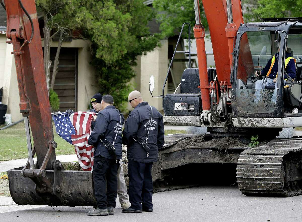 Firefighters from Hillsborough County, Fla., fold a U.S. flag after removing it from a home in Seffner that was being razed after a sinkhole opened up underneath it and swallowed a man living there.