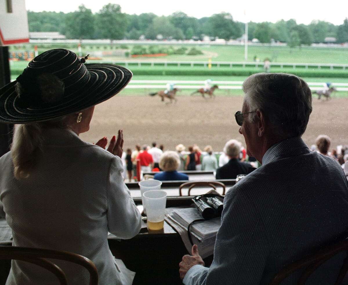 Times Union Staff Photo by CINDY SCHULTZ -- THURSDAY, JULY 30, 1998 -- SARATOGA SPRINGS, NY -- Charles and Patricia Beyrer of Oak River Stables watch the second race Thursday from box seats they've owned for 11 years at Saratoga Race Course.