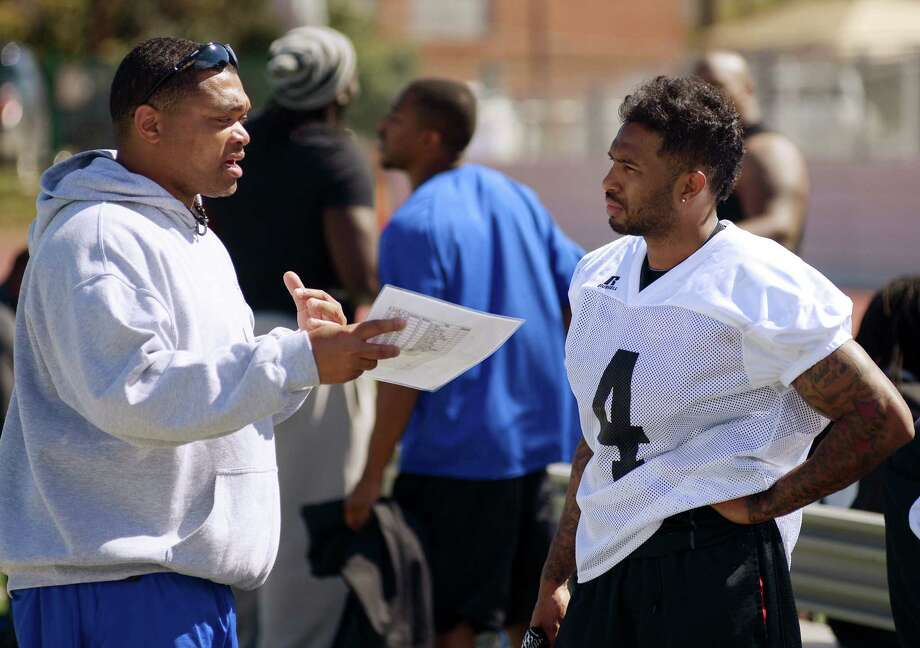 Talons offensive coordinator Ray Philyaw (left) talks to Robert Gill, a former Judson and Texas State athlete, during the team's first practice Sunday at Incarnate Word's Benson Stadium. Photo: Darren Abate / For The Express-News