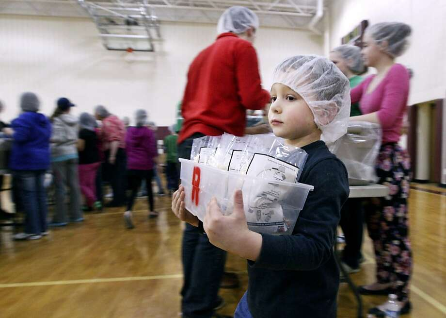 In this March 2, 2013 photo, volunteer Nick Labrozzi, 5, carries filled bags of food to a weighing station at Handley High School for the Stop Hunger Now program in Winchester, Va.  Photo: Scott Mason, Associated Press
