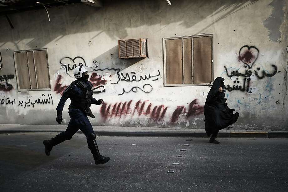 A Bahraini policeman runs after a woman during clashes with protesters, who tried to reach Salmaniya hospital to retrieve the body of Mahmud al-Jaziri, in the village of Zinj, a suburb of Manama, on March 2, 2013. Jaziri, 20, succumbed to his wounds on February 21 after he was shot during clashes between police and protesters marking the second anniversary of the February 14, 2011 uprising. His family says Bahraini authorities have not handed over his body because of a dispute over the location of the planned funeral.  Photo: Mohammed Al-shaikh, AFP/Getty Images