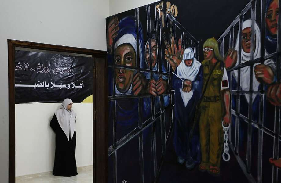 "A Palestinian guide looks at a mural depicting prisoners at an art exhibition called ""souls, no pictures"" examining the lives of Palestinian prisoners held in Israeli jails, in Gaza City, Sunday, March 3, 2013. The exhibition, organized by the Hamas Association of Released Prisoners, includes a collection of photographs, smuggled from jails, showing Palestinian prisoners held in Israel. Arabic sign, partially seen, reads ""exhibition: souls no pictures, welcome visitors.""  Photo: Hatem Moussa, Associated Press"