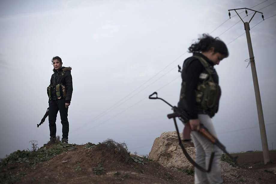 Kurdish female members of the Popular Protection Units stand guard at a check point near the northeastern city of Qamishli, Syria, Sunday, March 3, 2013.  Photo: Manu Brabo, Associated Press