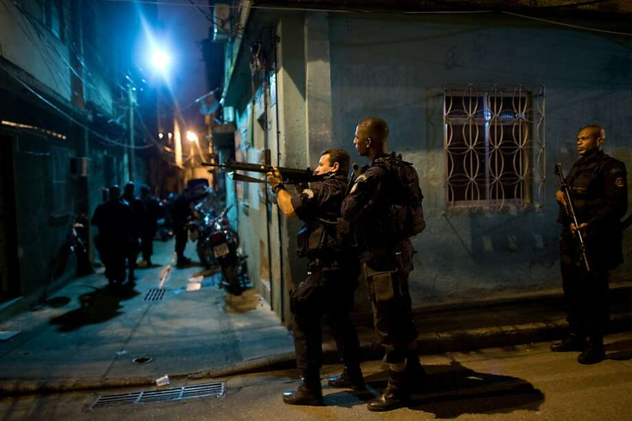 A Brazilian police elite unit personnel patrol during an operation at Caju shantytown in Rio de Janeiro, Brazil, early morning March 3, 2013. Brazilian police on Sunday occupied crime-infested slums near Rio de Janeiro's international airport and seaport as part of efforts to drive out drug traffickers ahead of the 2014 World Cup. The operation, which began at 4:55 am local time (0755 GMT), involved more than 1,300 police and members of the military backed by mechanized units of the Brazilian navy, which entered the favelas of Caju and Barreira do Vasco and seized control of their narrow streets.  Photo: Christophe Simon, AFP/Getty Images