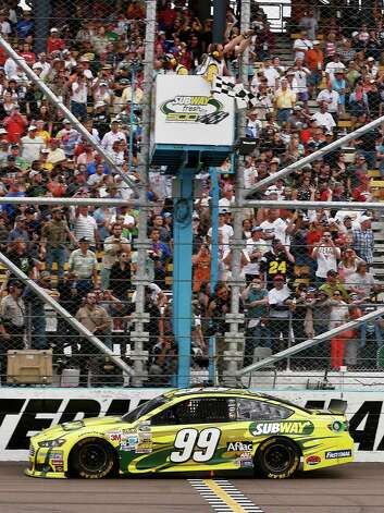 Carl Edwards takes the checkered flag to win the NASCAR Sprint Cup Series auto race, Sunday, March 3, 2013, in Avondale, Ariz. (AP Photo/Ross D. Franklin) Photo: Ross D. Franklin