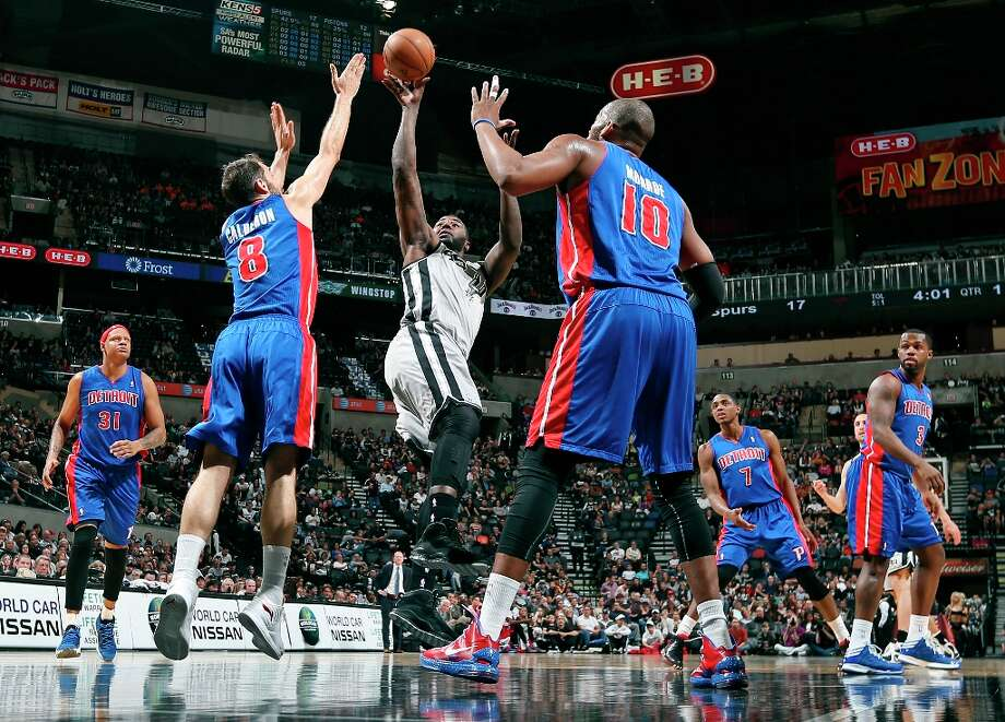 The Spurs' DeJuan Blair shoots between Detroit Pistons' Jose Calderon and Detroit Pistons' Greg Monroe during first half action Sunday, March 3, 2013 at the AT&T Center. Photo: Edward A. Ornelas, San Antonio Express-News / © 2013 San Antonio Express-News