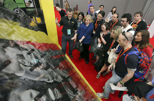 People try to win an OtterBox phone case during an SXSW show in Austin last year. Organizers expect attendance at this year's SXSW Interactive Festival to be more than 27,000. Photo: San Antonio Express-News File Photo