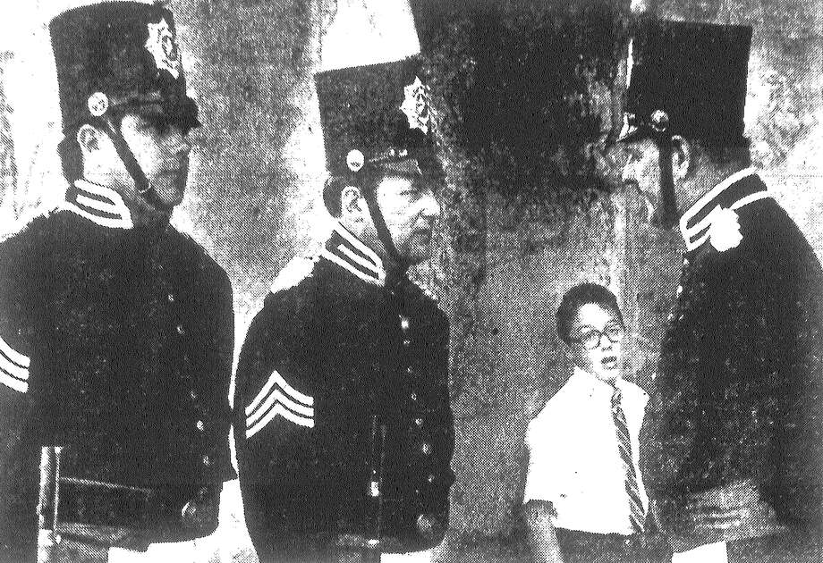 Robert Benevides, 11, seems in awe of the Texas Guard of Sons of the Republic of Texas as they wait for ceremonies honoring the Alamo heroes to begin in front of San Fernando Cathedral. Guard members, from left, are Joseph W. Bueno, Chuck Chiappina and Jim Oberman. Published in the San Antonio Light March 7, 1983. Photo: File Photo