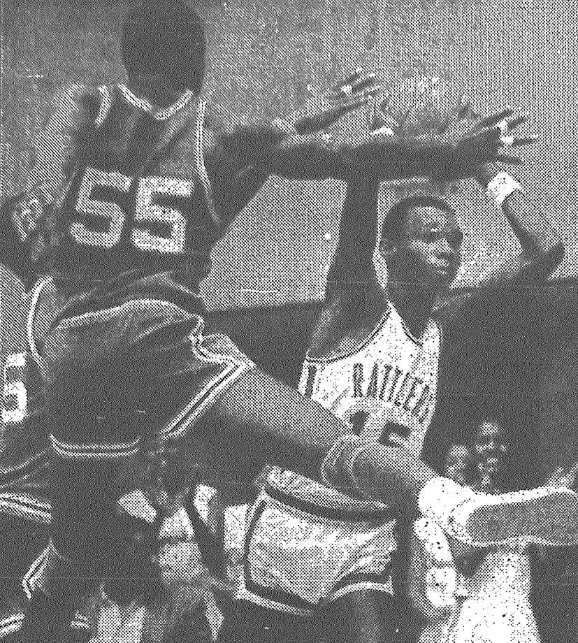 San Marcos' Anthony Gordon passes the ball around Sam Houston's Don Royster in San Marcos' 59-41 victory in the Class 5A regional boys' basketball finals. Published in the San Antonio Express March 6, 1983. Photo: File Photo