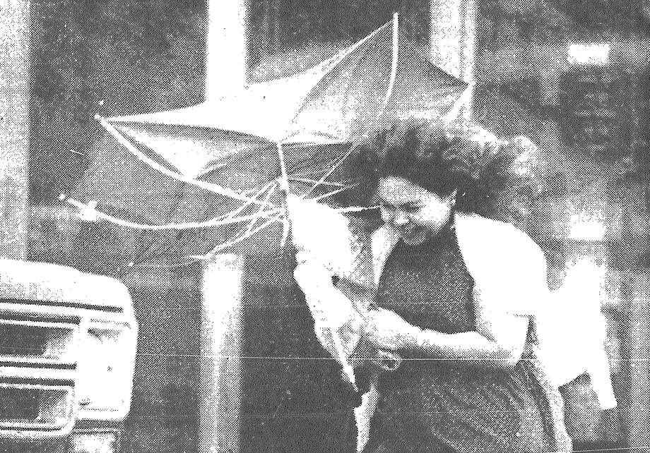 Gloria Rivera grimaces as a gust of wind turns her umbrella inside out in downtown San Antonio Wednesday, when afternoon winds averaged about 20 mph and gusts clocked in as high as 40 mph. Published in the San Antonio Express March 17, 1983. Photo: File Photo