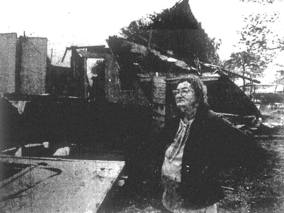 Lillie Howerton, owner of the house in the 1200 block of DuPont, views the remains of the dwelling, which was destroyed when a space heater exploded. Leonard Anderson, 43, was hospitalized with extensive first- and second-degree burns after repeatedly dashing into the burning home to rescue his wife and four young children, who were also hospitalized. Published in the San Antonio Light March 14, 1983. Photo: File Photo