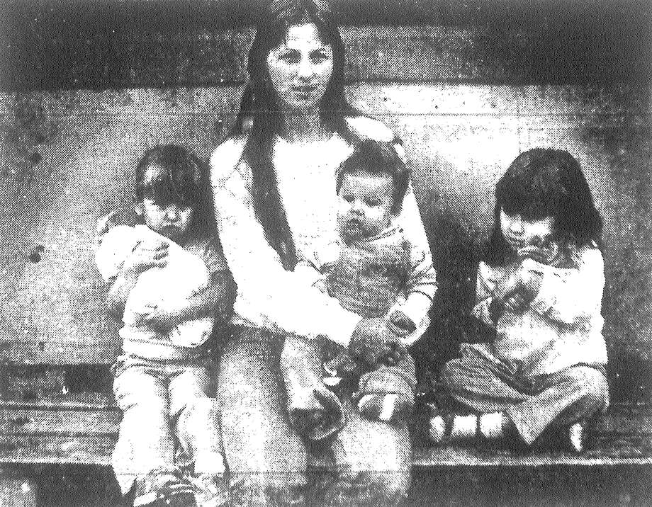 Debbie McPherson holds son, Jason, 5 months, while daughters Carol (left), 4, and Shannon, 3, cuddle baby dolls. The family was waiting for a bus after dropping off their entries in The Birthday Game. Published in the San Antonio Light March 24, 1983. Photo: File Photo