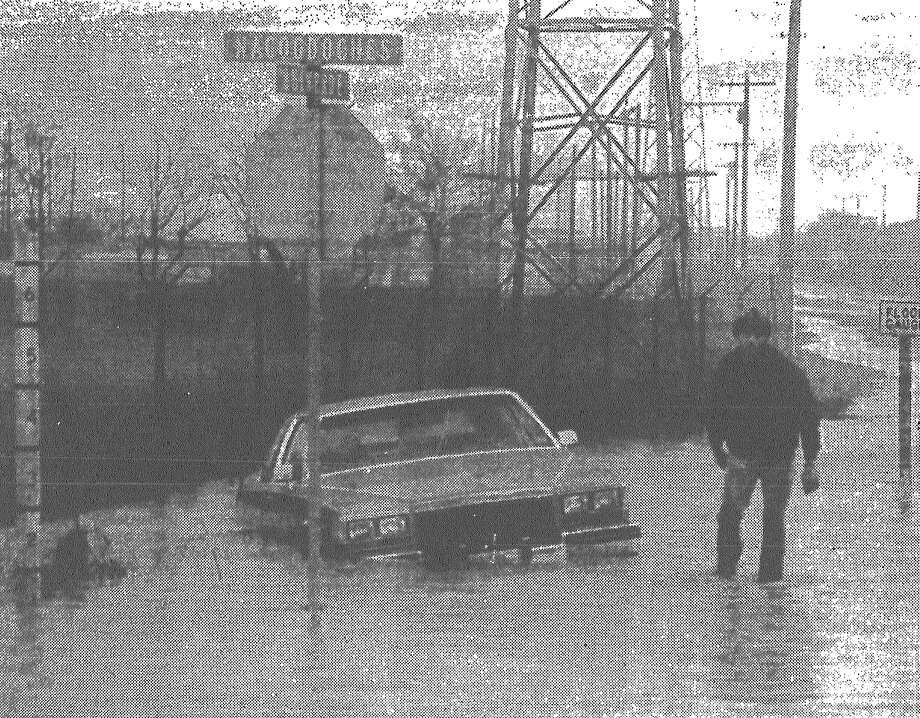 Jeff Agee of City Towing prepares to free Lynn Monaco's car, which was caught by floodwaters at Nacogdoches and Bulverde roads. Published in the San Antonio News March 23, 1983. Photo: File Photo