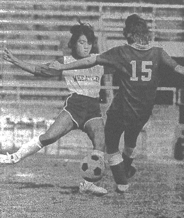 Wheatley's Myrna Estopia drives the ball against Lee's Adrian McMillian, who is unable to block it. Lee slapped Wheatley, 4-0, in the Regional IV finals to get a shot at Round Rock Westwood. Published in the San Antonio Express March 31, 1983. Photo: File Photo