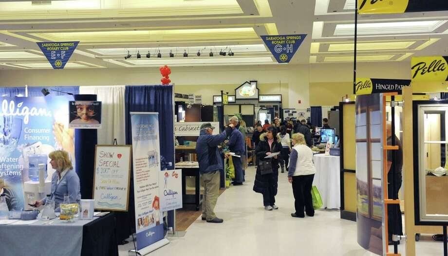 Visitors look over the different booths at the 2013 Saratoga Springs Rotary Home and Lifestyle Show at the Saratoga Springs City Center on Sunday, March 3, 2012 in Saratoga Springs, NY.  This is the 40th year of the show, which is the Rotary's largest fundraising event of the year.  Proceeds from the show help th Rotary fund local groups and organizations in the community and allows the Rotary to fund a major gift each year at about $30,000.  The Rotary also gives student scholarships, last year giving away $45,000 in scholarships.  This years show had 120 vendors showing off home products and services.   (Paul Buckowski / Times Union) Photo: Paul Buckowski