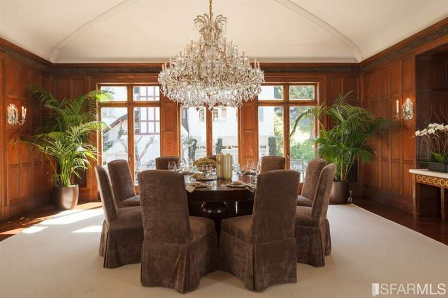 Grand chandelier over the formal dining room with wood paneled walls.