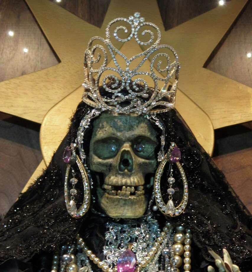 In this Feb. 12, 2013 photo, a statue of La Sante Muerte from an altar run by Arely Vazquez Gonzalez, a Mexican immigrant and transgender woman, is shown at inside a Queens, NY apartment.  La Santa Muerte, an underworld saint most recently associated with the violent drug trade in Mexico, now is spreading throughout the U.S. among a new group of followers ranging from immigrant small business owners to artists and gay activists. In addition to showing up at drug crime scenes, the once-underground icon has been spotted on passion candles in Richmond, Va. grocery stores. The folk saint's image can be seen inside New York City apartments, in Minneapolis religious shops and during art shows in Tucson, Ariz. Photo: Russell Contreras