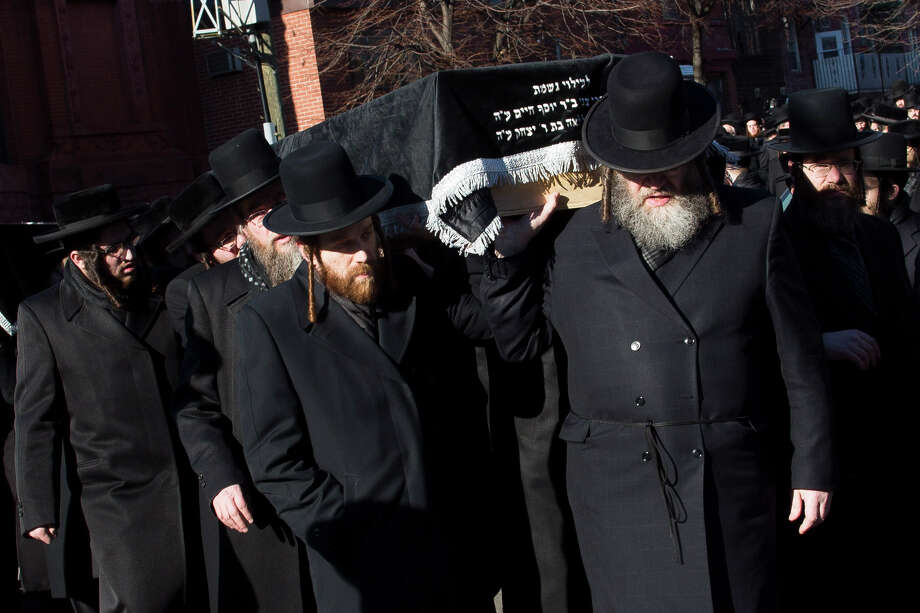 Members of the Satmar Orthodox Jewish community carry the coffins of two expectant parents who were killed in a car accident, Sunday, March 3, 2013, in the Brooklyn borough of New York. A driver struck the car the couple were riding in early Sunday morning, killing both parents while their baby, who was born prematurely, survived and is in critical condition. Photo: John Minchillo, AP / FR170537 AP