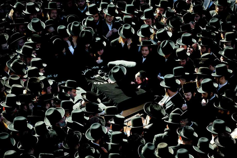 Members of the Satmar Orthodox Jewish community grieve over the coffins at the funeral for two expectant parents who were killed in a car accident, Sunday, March 3, 2013, in the Brooklyn borough of New York. A driver struck the car the couple were riding in early Sunday morning, killing both parents while their baby, who was born prematurely, survived and is in critical condition. Photo: John Minchillo, AP / FR170537 AP
