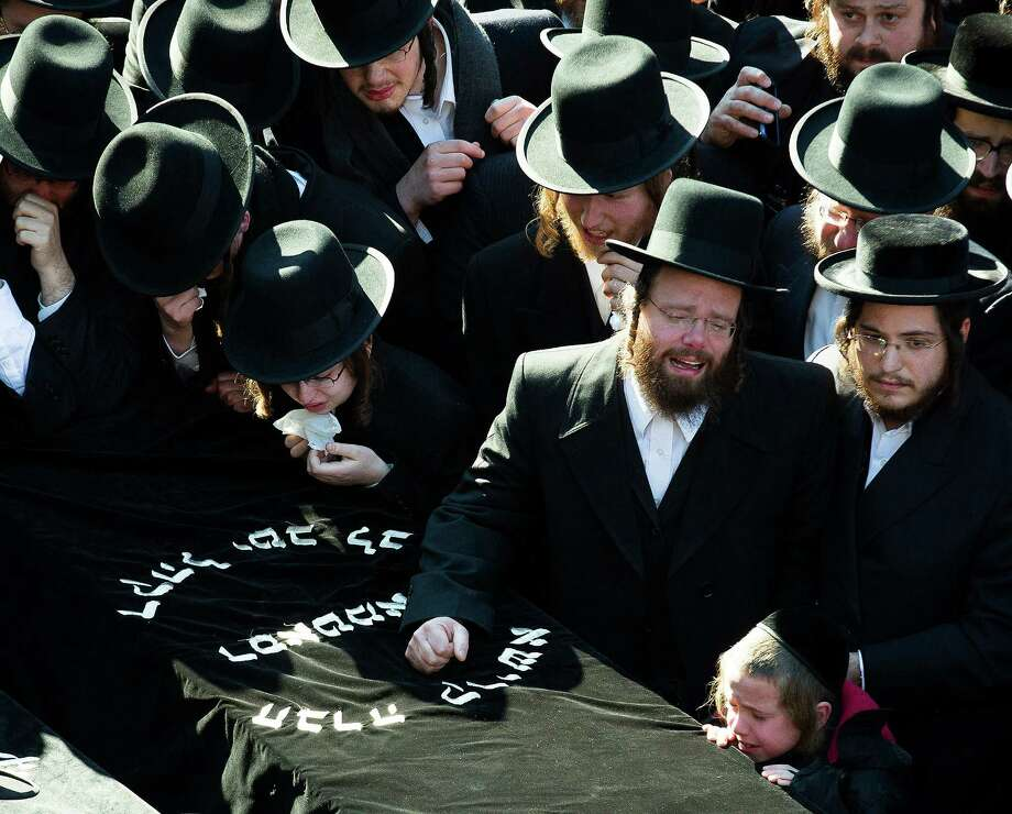 Members of the Satmar Orthodox Jewish community congregate for the funeral of two expectant parents who were killed in a car accident, Sunday, March 3, 2013, in the Brooklyn borough of New York. A driver struck the car the couple were riding in early Sunday morning, killing both parents while their baby, who was born prematurely, survived and is in critical condition. Photo: John Minchillo, AP / FR170537 AP