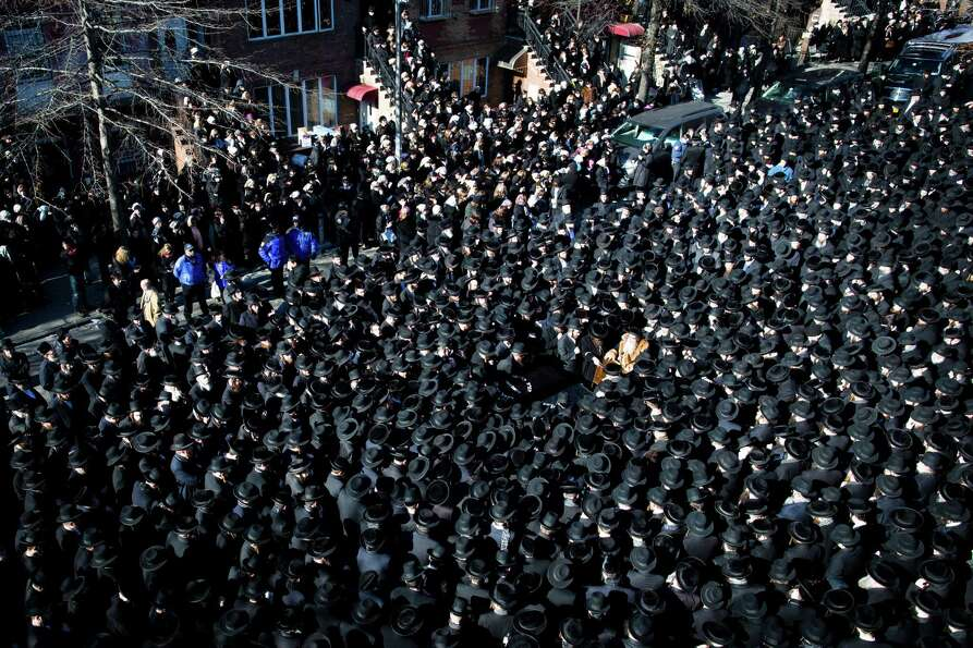 Members of the Satmar Orthodox Jewish community congregate for the funeral of two expectant parents