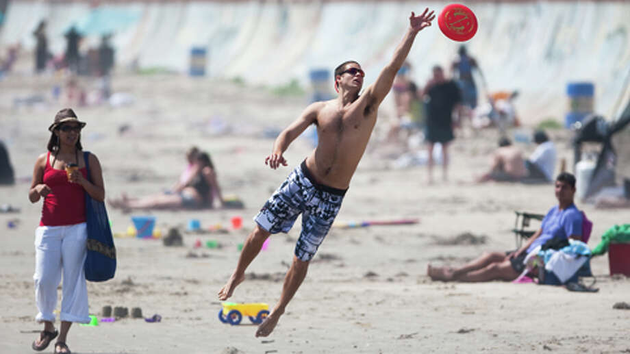 Josh Leuchtag, of Houston, reaches for a frisbee as he enjoys some sunshine with his girlfriend Lacey Truelove, of Houston, Tuesday, March 13, 2012, on the beach by Seawall Boulevard in Galveston. Photo: Nick De La Torre, . / © 2012  Houston Chronicle
