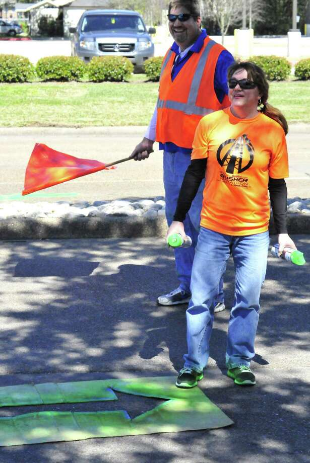 Gusher Marathon organizers and volunteers   joined by the mascot, Diesel - spent several hours Sunday spray painting arrows on the street for runners to follow during the fourth-annual marathon, half marathon and 5k race. Blue arrows are for those running the 5k and the green arrows are for those running the full and half marathon. The course and finish line will remain open for six hours and registration is open until Friday. Photo by Cassie Smith Photo: Cassie Smith