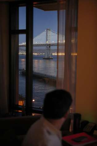 Artist Leo Villareal looks at the San Francisco Bay Bridge as he tests his Bay Lights installation from the Hotel Vitale. Photo: Carlos Avila Gonzalez, The Chronicle