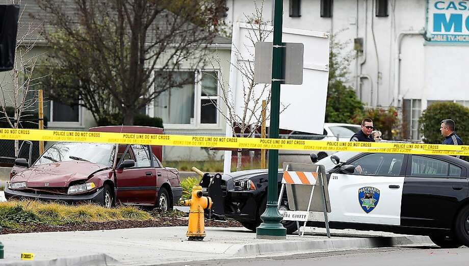 Police investigate the scene of an officer-involved shooting near an intersection, Sunday, March 3, 2013, in Hayward, Calif. A suspect tried to run down a Hayward police officer during a traffic stop early Sunday, police said. Photo: Aric Crabb, Associated Press