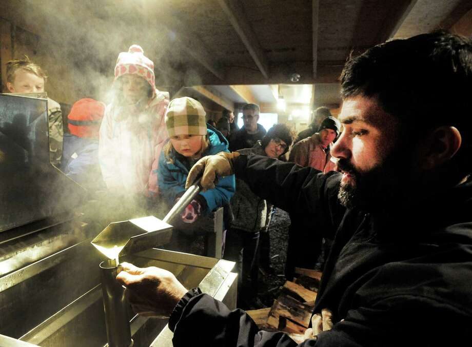 Visitors, including Fiona Cahill, 5, center, watch Lars Cherichetti test maple syrup in the Shugar Shack evaporator during New Pond Farm's maple syruping program Saturday, March 2, 2013 in Redding, Conn. Photo: Michael Duffy / The News-Times