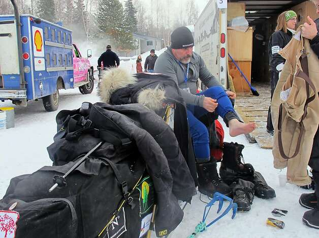 Scott Janssen, a musher whose family owns an Anchorage funeral home, changes into a dry pair of socks before the Iditarod Trail Sled Dog Race, Sunday, March 3, 2013, in Willow, Alaska. 65 teams will be making their way through punishing wilderness toward the finish line in Nome on Alaska's western coast 1,000 miles away.  Photo: Mark Thiessen, Associated Press