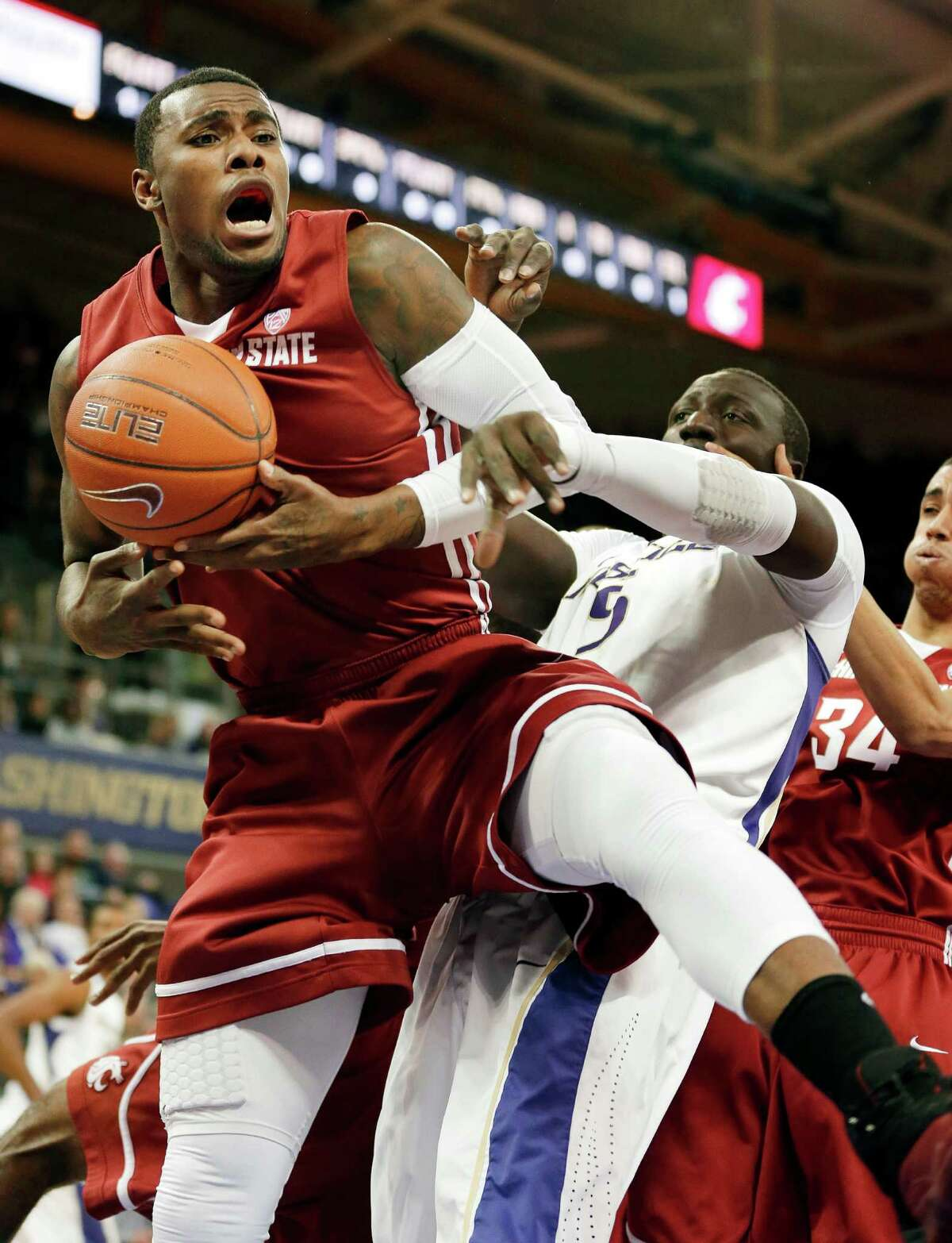 Washington State's D.J. Shelton, left, grabs a rebound over Washington's Aziz N'Diaye in the first half of an NCAA college basketball game on Sunday, March 3, 2013, in Seattle.