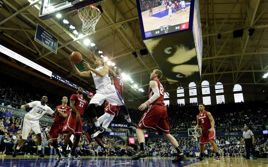Washington's Abdul Gaddy shoots over the defense of Washington State's D.J. Shelton, center, and Brock Motum, second from right, in the first half of an NCAA college basketball game, Sunday, March 3, 2013, in Seattle. Photo: Ted S. Warren / Associated Press