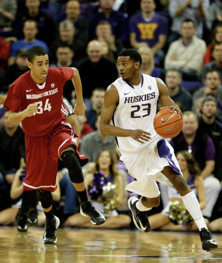 Washington's C.J. Wilcox, right, dribbles the ball against Washington State's Dexter Kernich-Drew, left, in the second half of an NCAA college basketball game, Sunday, March 3, 2013, in Seattle. Photo: Ted S. Warren / Associated Press